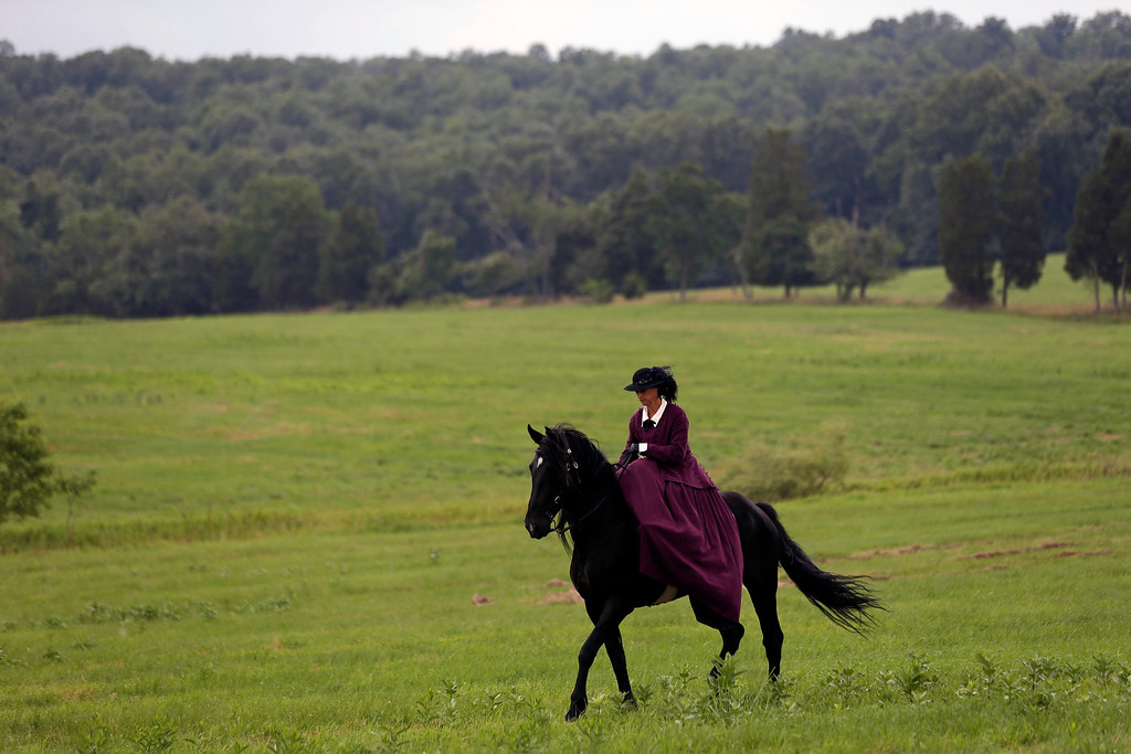 . Cindy Westbroek of Clearfield, Utah rides her horse at Bushe Farm during ongoing activities commemorating the 150th anniversary of the Battle of Gettysburg, Thursday, June 27, 2013, in Gettysburg, Pa. (AP Photo/Matt Rourke)