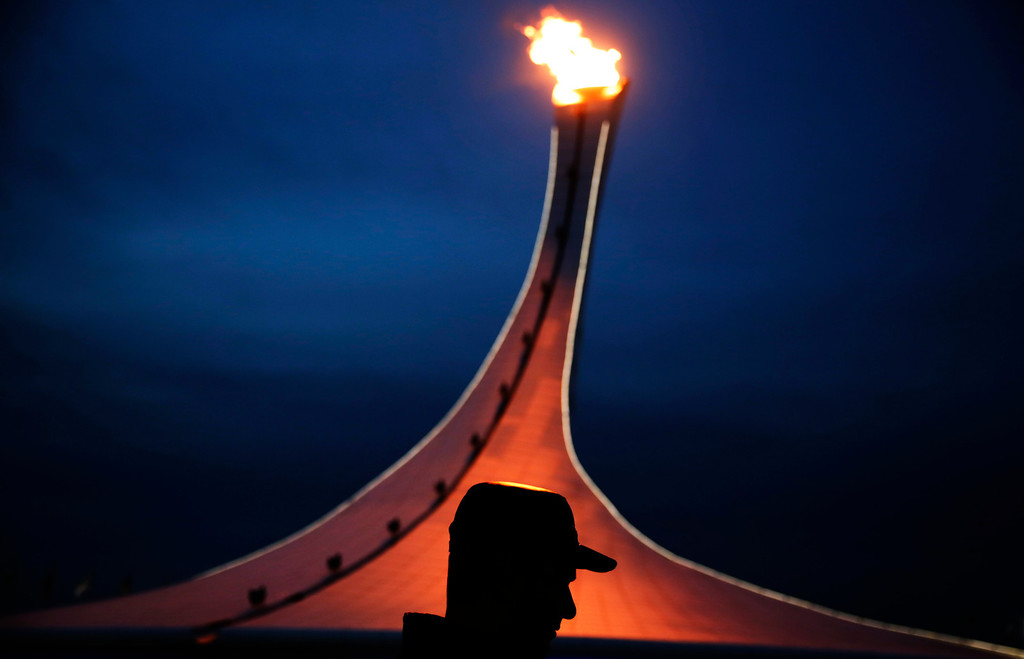 . A visitor to Olympic Park is silhouetted while walking past the Olympic cauldron at the 2014 Winter Olympics, Thursday, Feb. 20, 2014, in Sochi, Russia. (AP Photo/David Goldman)