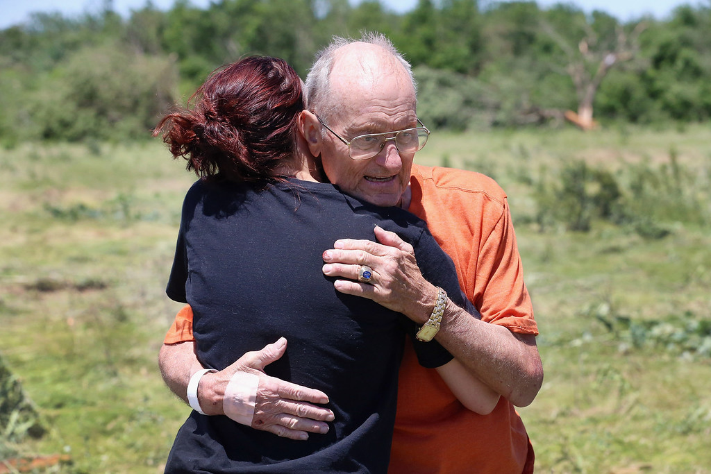 . EL RENO, OK - JUNE 01: Kalia Robbins (L) hugs her great uncle Bill Thesing who was injured while in his home when a tornado hit on June 1, 2013 in El Reno, Oklahoma. The tornado ripped through the area killing at least nine people, injuring many others and destroying homes and buildings.  (Photo by Joe Raedle/Getty Images)