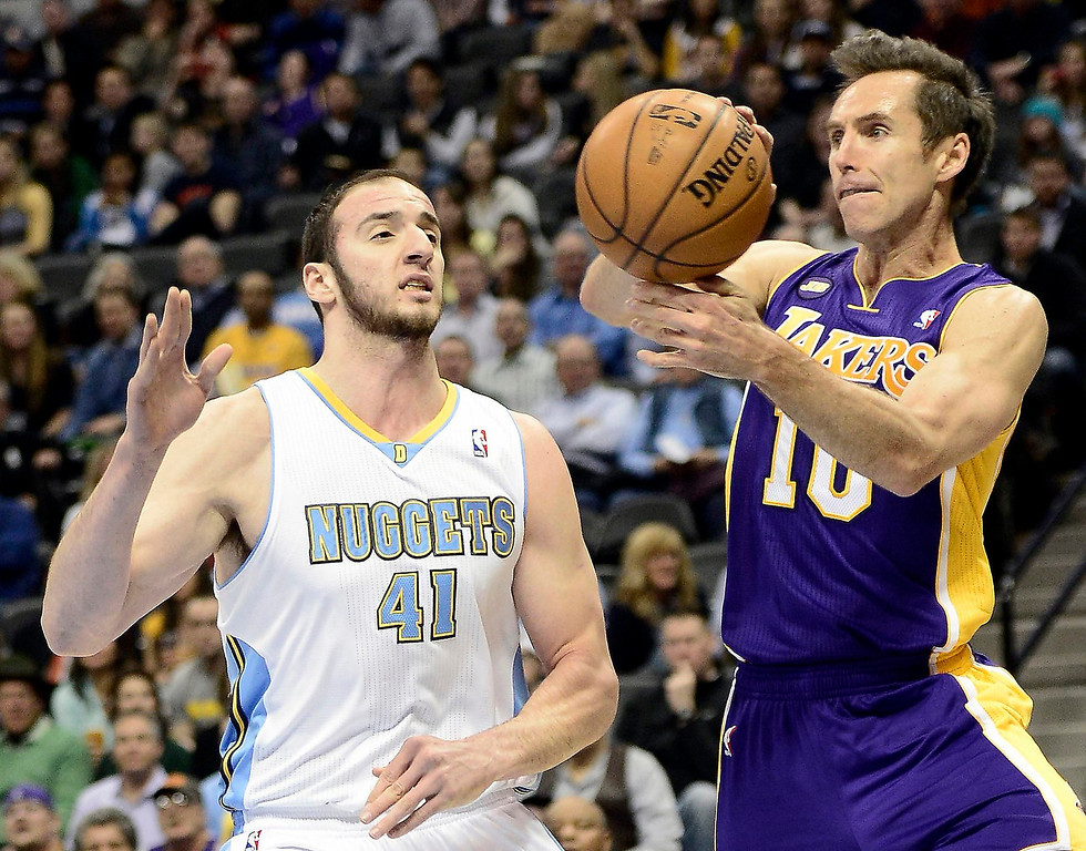 . Los Angeles Lakers Steve Nash (R) passes the ball away from Denver Nuggets Kosta Koufos (L) during their NBA basketball game in Denver, Colorado February 25, 2013.   REUTERS/Mark Leffingwell