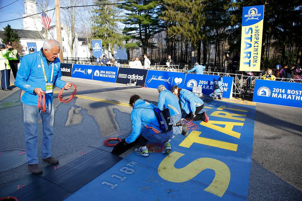 . Race officials wire the electronics for the start line before the 118th Boston Marathon begins Monday, April 21, 2014 in Hopkinton, Mass. (AP Photo/Stephan Savoia)