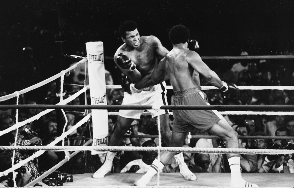. Challenger Muhammad Ali winces as he is hit with a powerful left jab to the body by defending world champion George Foreman in their WBA/WBC championship bout in Kinshasa, Zaire, on October 30, 1974. Ali regained the heavyweight crown by knocking out Foreman in the eighth round of the fight dubbed \'Rumble in the Jungle.\' (AP Photo)