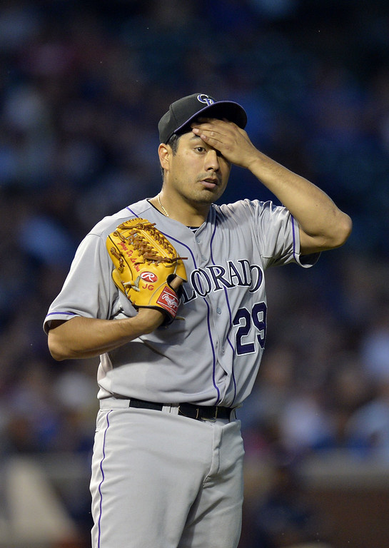 . Starting pitcher Jorge De La Rosa #29 of the Colorado Rockies wipes his head as he stands on the mound during the second inning against the Chicago Cubs on July 29, 2014 at Wrigley Field in Chicago, Illinois.  (Photo by Brian Kersey/Getty Images)
