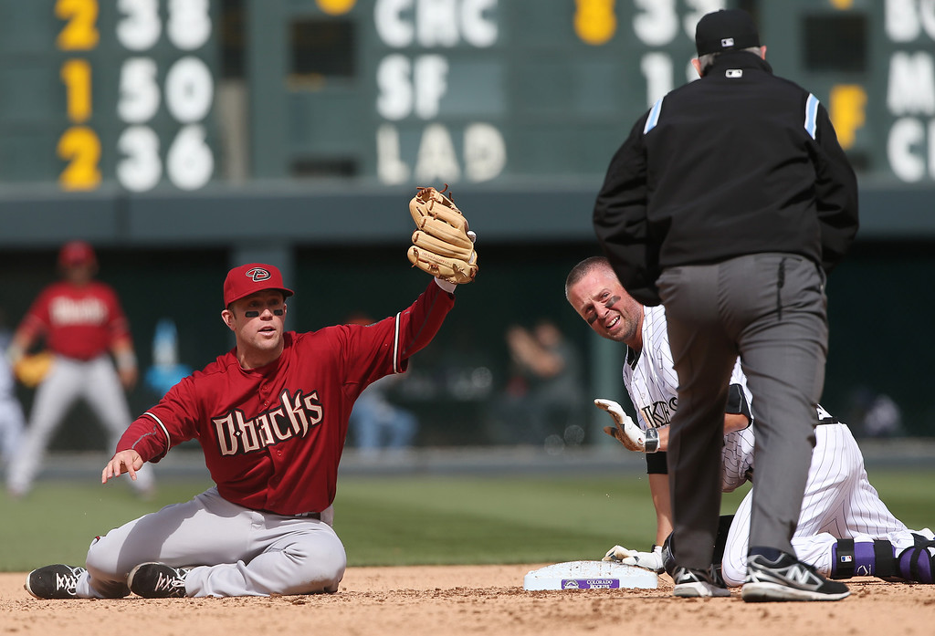 . Arizona Diamondbacks second baseman Aaron Hill, left, holds up glove as he looks or call from second base umpire Mike Winters after Colorado Rockies\' Michael Cuddyer, right, slide into second base with a double in the fourth inning of a baseball game in Denver on Sunday, April 6, 2014. (AP Photo/David Zalubowski)