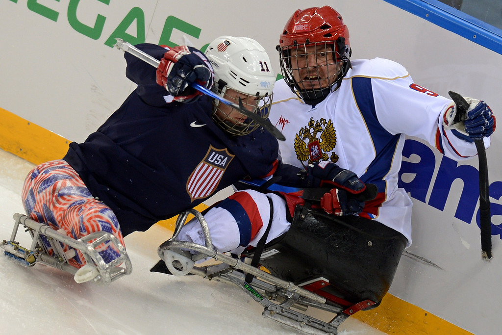. Russia\'s Konstantin Shikhov (R) vies with USA\'s Tyler Carron during the Sledge Hockey match between Russia and USA at XI Paralympic Olympic games in the Shayba stadium close to city of Sochi on March 11, 2014. AFP PHOTO/KIRILL KUDRYAVTSEV