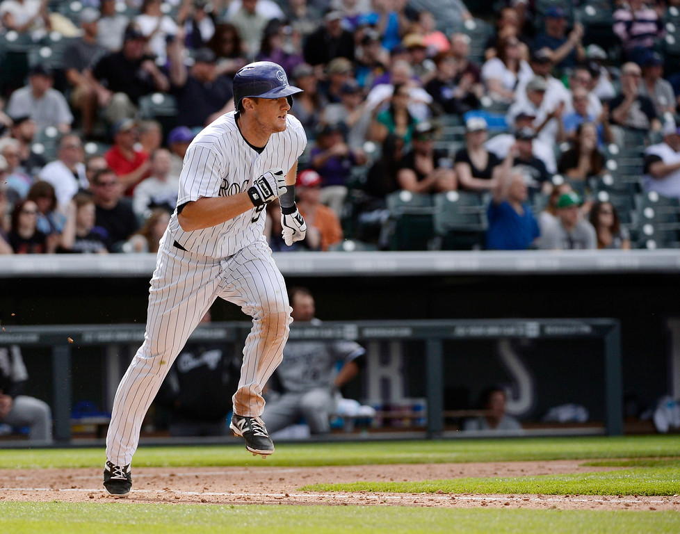 . Colorado Rockies second baseman, DJ LeMahieu, heads to first base after hitting an RBI double to score teammates Drew Stubbs and Nolan Arenado, to take the lead in the 8th inning against the Chicago White Sox at Coors Field Wednesday afternoon, April 09, 2014. The Rockies went on to win 10-4. (Photo By Andy Cross / The Denver Post)