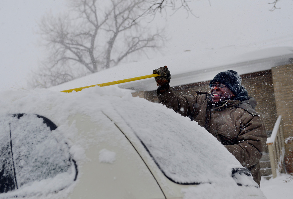 . LITTLETON, CO. - MARCH 23:  George Marsh uses a broom to clear the snow from his car outside his home in Englewood, CO March 23, 2013. The Saturday forecast calls for snow accumulation of 9 to 12 inches with highs in the lower to mid 20s. (Photo By Craig F. Walker/The Denver Post)