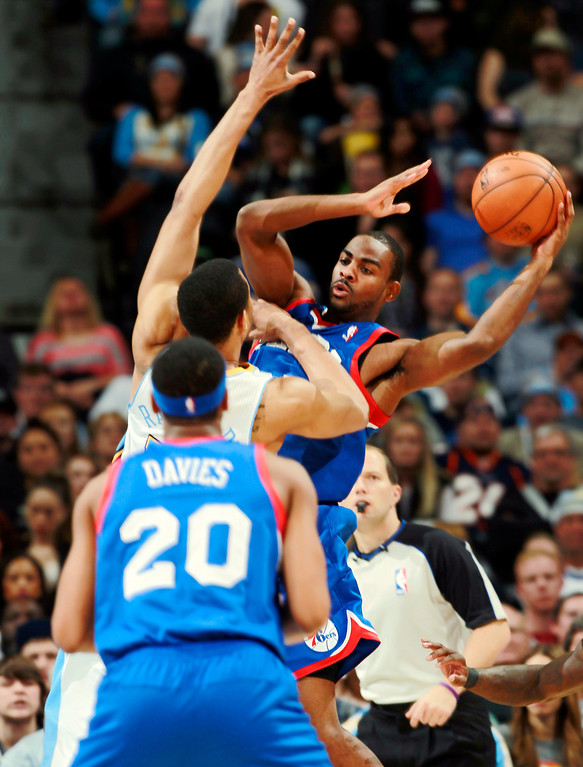 . Philadelphia 76ers guard Elliot Williams, back, looks to pass to forward Brandon Davies, front, as Denver Nuggets forward Anthony Randolph covers in the fourth quarter of the Sixers\' 114-102 victory in an NBA basketball game in Denver on Wednesday, Jan. 1, 2014. (AP Photo/David Zalubowski)
