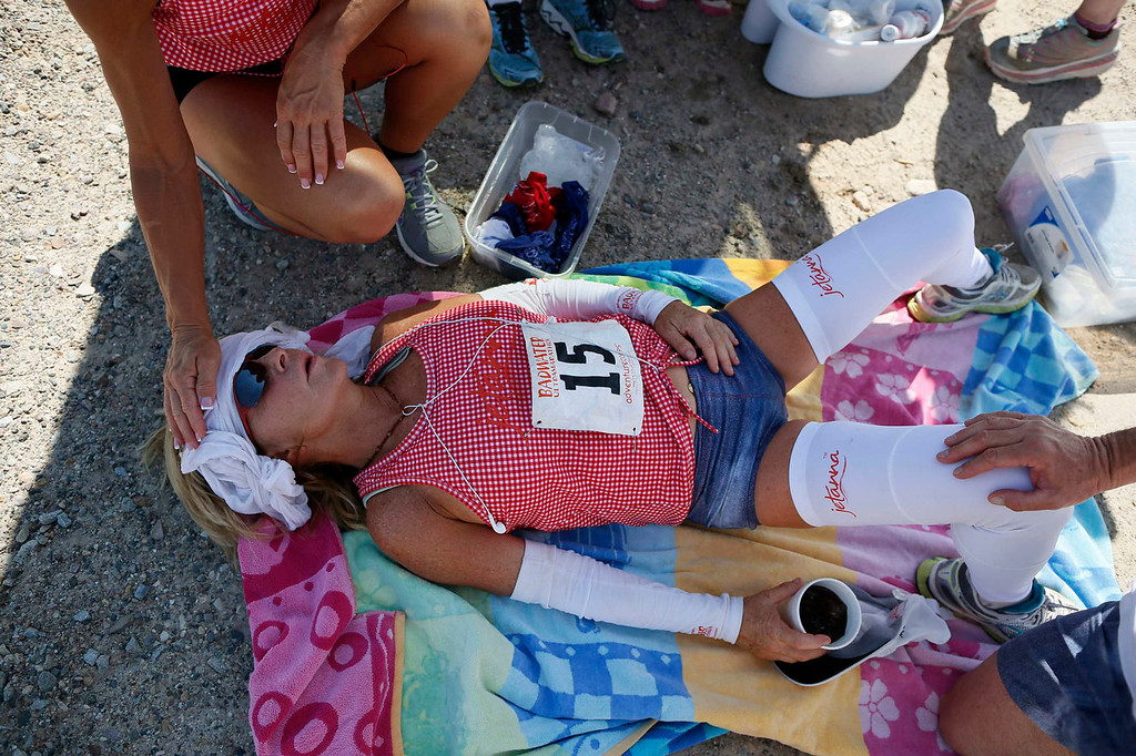 . Shannon Farar-Griefer, 52, of Hidden Hills, California, lies by the side of the road during the Badwater Ultramarathon in Death Valley National Park, California July 15, 2013. The 135-mile (217 km) race, which bills itself as the world\'s toughest foot race, goes from Death Valley to Mt. Whitney, California in temperatures which can reach 130 degrees Fahrenheit (55 Celsius). Farar-Griefer, who has multiple sclerosis, was hoping for her sixth finish in the race, but dropped out near mile 58. Picture taken July 15, 2013.   REUTERS/Lucy Nicholson