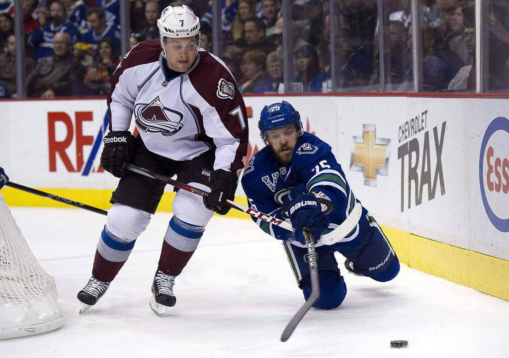 . Andrew Ebbett #25 of the Vancouver Canucks reaches for the loose puck after getting knocked down by John Mitchell #7 of the Colorado Avalanche during the second period in NHL action on March 28, 2013 at Rogers Arena in Vancouver, British Columbia, Canada.  (Photo by Rich Lam/Getty Images)