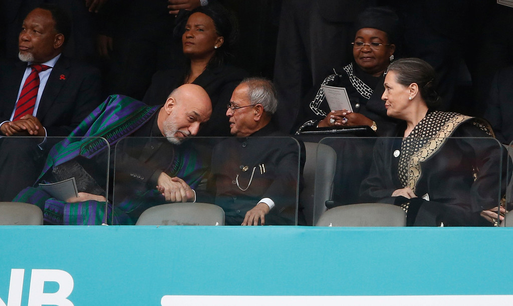 . Afghanistan President Hamid Karzai, left, shakes hands with Indiaís President Pranab Mukherjee as Sonia Gandhi looks on during the memorial service for former South African president Nelson Mandela at the FNB Stadium in Soweto near Johannesburg, Tuesday, Dec. 10, 2013. (AP Photo/Matt Dunham)