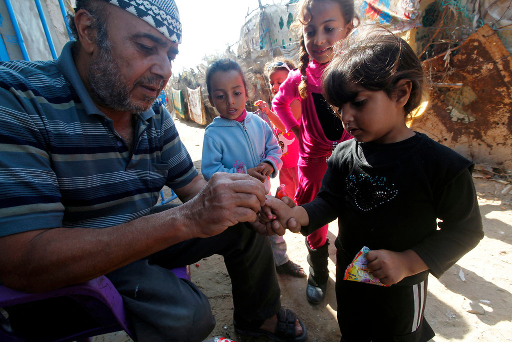 . In this Thursday, Oct. 17, 2013 photo, Salih Alwadiya, 61, left, paints the fingernails of his granddaughter Razan, 4, after she and other children received traditional gifts of toys while celebrating the third day of the Muslim festival of Eid al-Adha in front of their family house in Gaza City. Alwadiya is unemployed but used  to work in Israel, and was once wounded by shrapnel during an air strike on Gaza. Later, his right leg was amputated following a car accident. (AP Photo/Adel Hana)