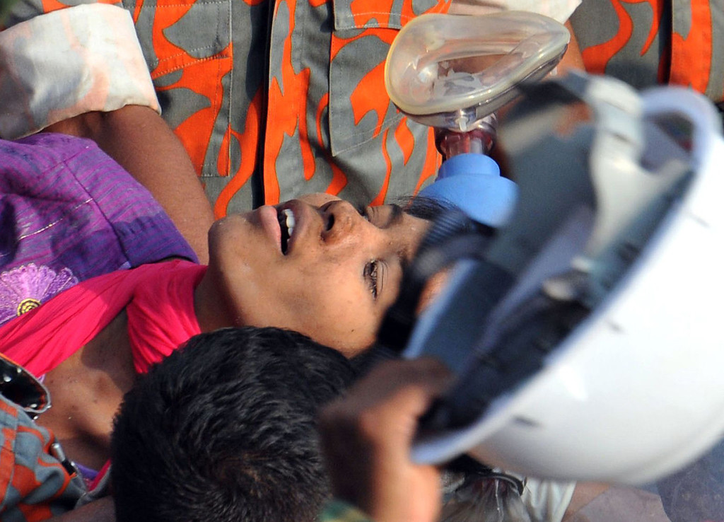 . Bangladeshi rescuers retrieve garment worker Reshma from the rubble of a collapsed building in Savar on May 10, 2013, seventeen days after an eight-story building collapsed.  AFP PHOTO/STRSTRDEL/AFP/Getty Images