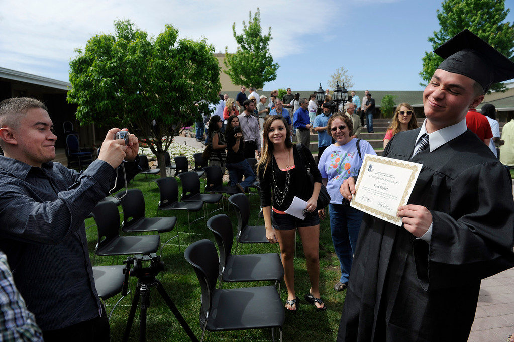 . Graduate Ryan Ruybal, right, gets his photo taken with his certificate by friend Del Maestas.  (Photo By Kathryn Scott Osler/The Denver Post)