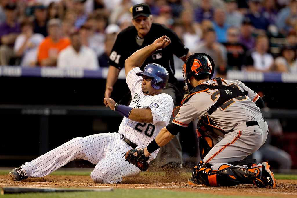. DENVER, CO - MAY 17:  Wilin Rosario #20 of the Colorado Rockies scores before catcher Buster Posey #28 of the San Francisco Giants can apply the tag as home plate umpire Bob Davidson looks on during the second inning at Coors Field on May 17, 2013 in Denver, Colorado.  (Photo by Justin Edmonds/Getty Images)