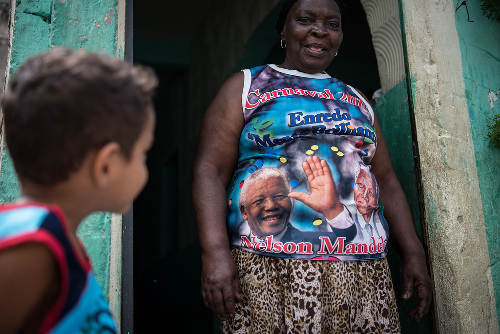 ". Denaide Alves da Fonseca wears a shirt of her carnival drum group ""Batuqueiros do Mandela\"" at Mandela shantytown (favela) in Rio de Janeiro, Brazil, on December 6, 2013. The shantytown was named after Mandela to commemorate his discharge from prison in 1990. AFP PHOTO / YASUYOSHI CHIBA/AFP/Getty Images"