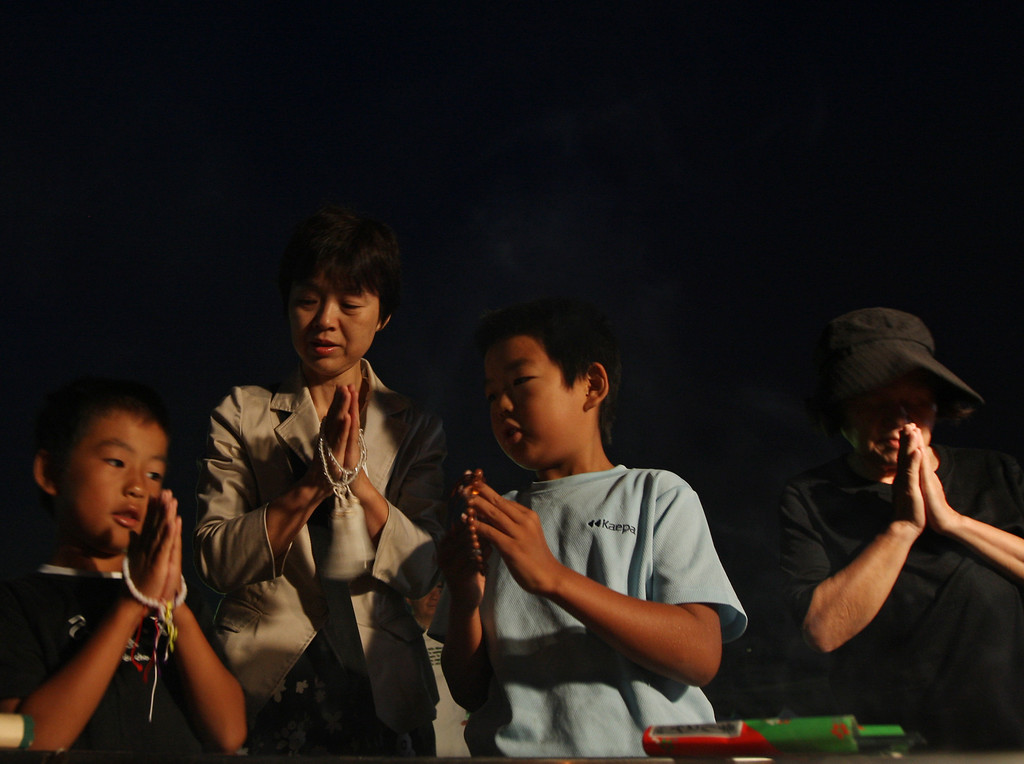 . A mother and her children pray for atomic bomb victims victims at the Hiroshima Peace Memorial Park on the day of the 68th anniversary of the atomic bombing of Hiroshima on August 6, 2013 in Hiroshima, Japan. (Photo by Buddhika Weerasinghe/Getty Images)