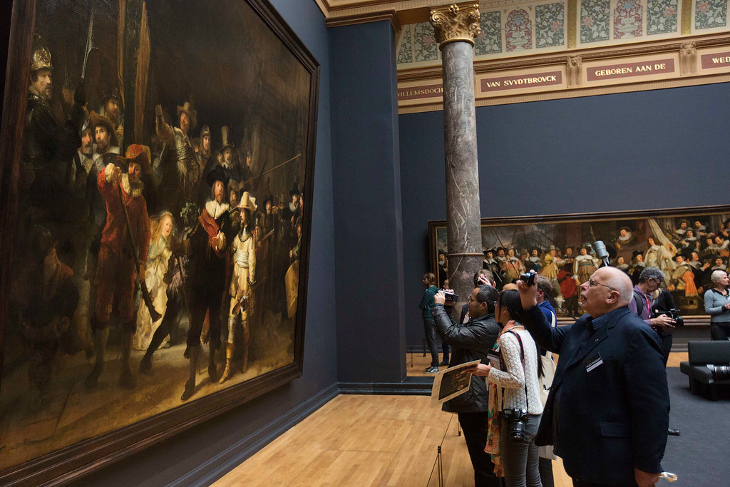 . Members of the media take pictures of the Nightwatch by Rembrandt in the Night Watch Gallery of the Rijksmuseum the Amsterdam April 4, 2013. The Royal celebrations in the Netherlands this week put the country and the capital Amsterdam on front pages and television screens around the world with an orange splash. There\'s plenty to see and do in 48 hours in this compact city, where the world-famous Rijksmuseum only recently reopened after an extensive renovation. Picture taken April 4, 2013. REUTERS/Michael Kooren
