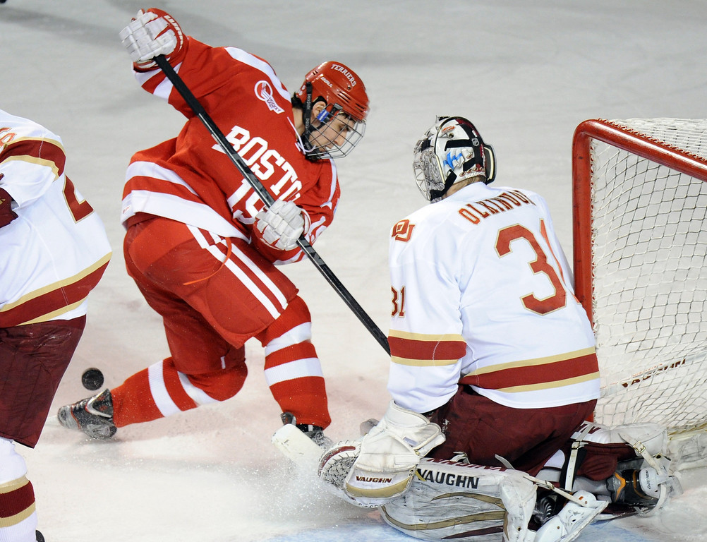 . University of Denver goalie Juho Olkinuora (31), right, blocks a shot from  Boston University\'s Matt Nieto (19) in the 1st period of the game at Magness Arena on in Denver on Saturday, Dec. 29, 2012. Hyoung Chang, The Denver Post