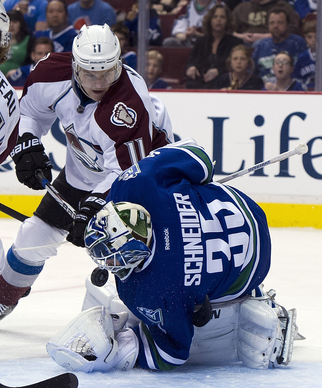 . Goalie Cory Schneider #35 of the Vancouver Canucks scrambles to block the puck as Jamie McGinn #11 of the Colorado Avalanche digs for the rebound during the first period in NHL action on March 28, 2013 at Rogers Arena in Vancouver, British Columbia, Canada.  (Photo by Rich Lam/Getty Images)