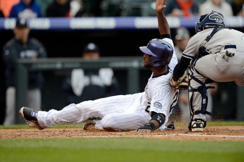 . Chris Stewart (19) of the New York Yankees cant\' apply the tag as Dexter Fowler (24) of the Colorado Rockies slides in safe at home to score during the first inning May 9, 2013 at Coors Field. (Photo By John Leyba/The Denver Post)