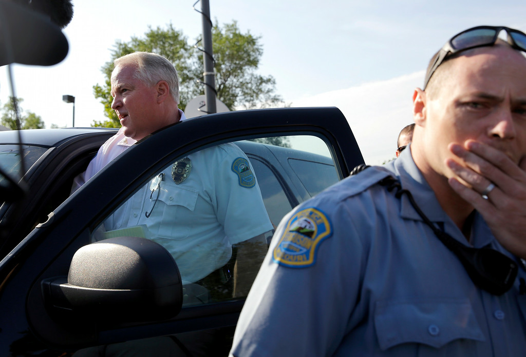 . Ferguson Police Chief Thomas Jackson, left, gets in a vehicle to drive away after releasing the name of the the officer accused of fatally shooting Michael Brown, an unarmed black teenager, during a news conference Friday, Aug. 15, 2014, in Ferguson, Mo.  Jackson announced that the officer\'s name is Darren Wilson. (AP Photo/Jeff Roberson)
