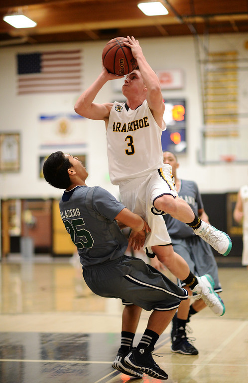 . CENTENNIAL, CO. JANUARY 18: Nick Farmen of Arapahoe High School (3) aims basket over Tyler Stevenson of Overland High School (25) in the 1st half of the game at Arapahoe High School. Centennial Colorado. January 18. 2014. Arapahoe won 62-54.  (Photo by Hyoung Chang/The Denver Post)