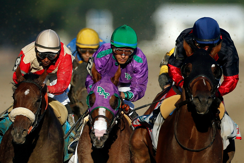 . California Chrome, center, is flanked by Wicked Strong, left, and Tonalist, right, as they run down the backstretch during the 146th running of the Belmont Stakes horse race at Belmont Park, Saturday, June 7, 2014, in Elmont, N.Y.  Tonalist went on to win the race, denying California Chrome the Triple Crown victory. (AP Photo/Jason DeCrow)