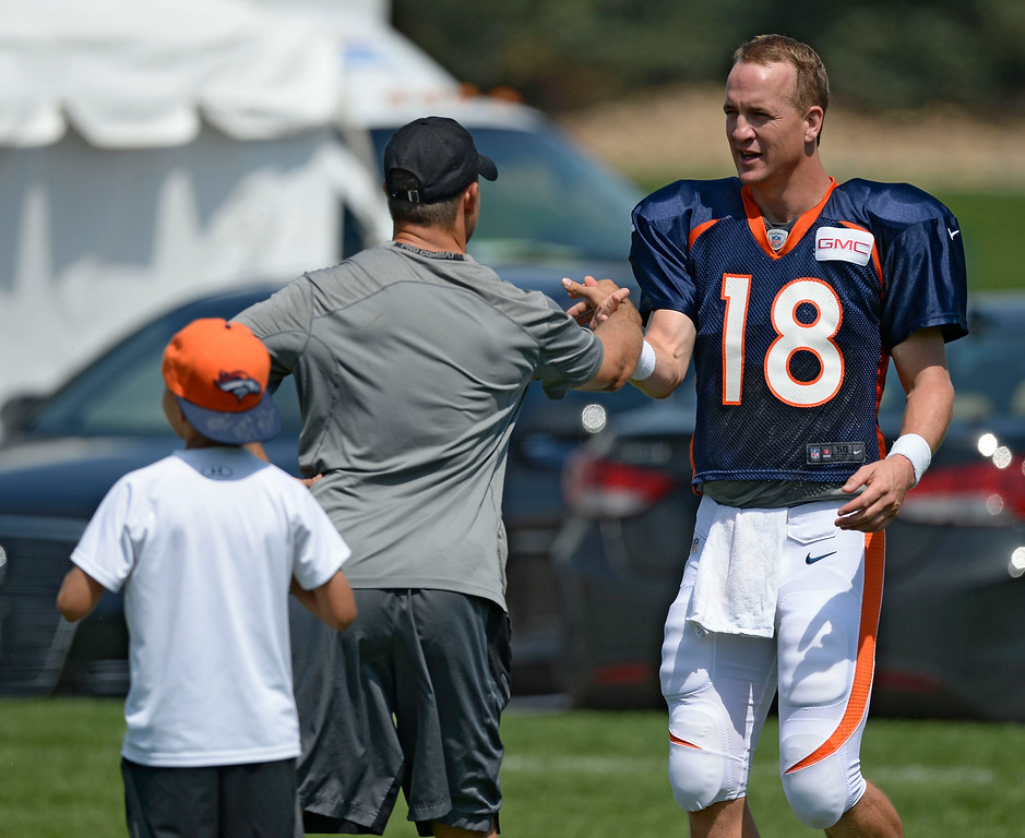 . Denver Broncos quarterback Peyton Manning (18) shakes hand with Brandon Stokley after practice on day five of the Denver Broncos 2014 training camp July 28, 2014 at Dove Valley. (Photo by John Leyba/The Denver Post)