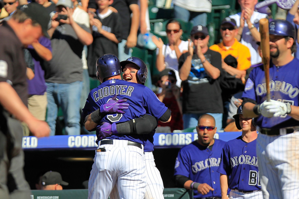 . Colorado Rockies\' Troy Tulowitzki hugs teammate Michael Cuddyer after he hit a two run homer to tie the game at six during the seventh inning of a baseball game against the Los Angeles Dodgers Saturday June 1, 2013 in Denver. (AP Photo/Barry Gutierrez)