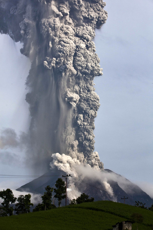 . Mount Sinabung spews pyroclastic smoke as seen from Tigapancur village in Karo district on November 14, 2013 in Medan, Sumatra, Indonesia. Up to 4,300 residents have been evacuated from five villages in North Sumatra due to the volcanic eruptions of Mount Sinabung. The volcano has been erupting for several days, spewing ash and lava 2.5 miles into the sky.  (Photo by Ulet Ifansasti/Getty Images)