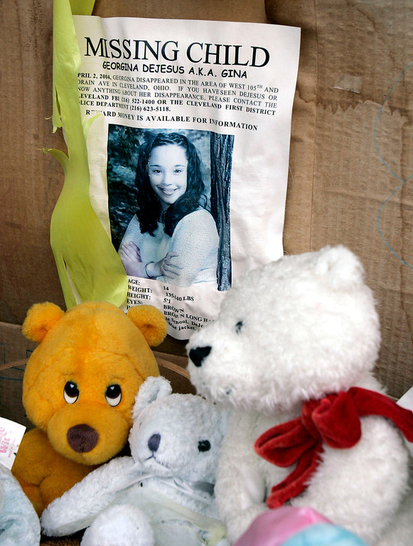 . In this March 3, 2006 file photo, a memorial for Gina DeJesus, who has been missing since April 2, 2004, rests alongside her house in Cleveland. Cleveland police say DeJesus, one of two women who went missing as teenagers about a decade ago has been found alive in a residential area about two miles (three kilometers) south of downtown. (AP Photo/Tony Dejak, File)