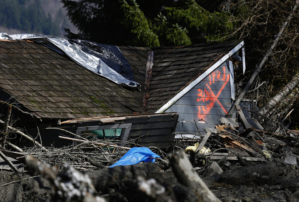 . The orange X on a house, destroyed in the mud, indicates it has been searched for people on Highway 530 next to mile marker 37 on March 23, 2014 near Arlington, Washington. (Photo by Lindsey Wasson/The Seattle Times-Pool/Getty Images)