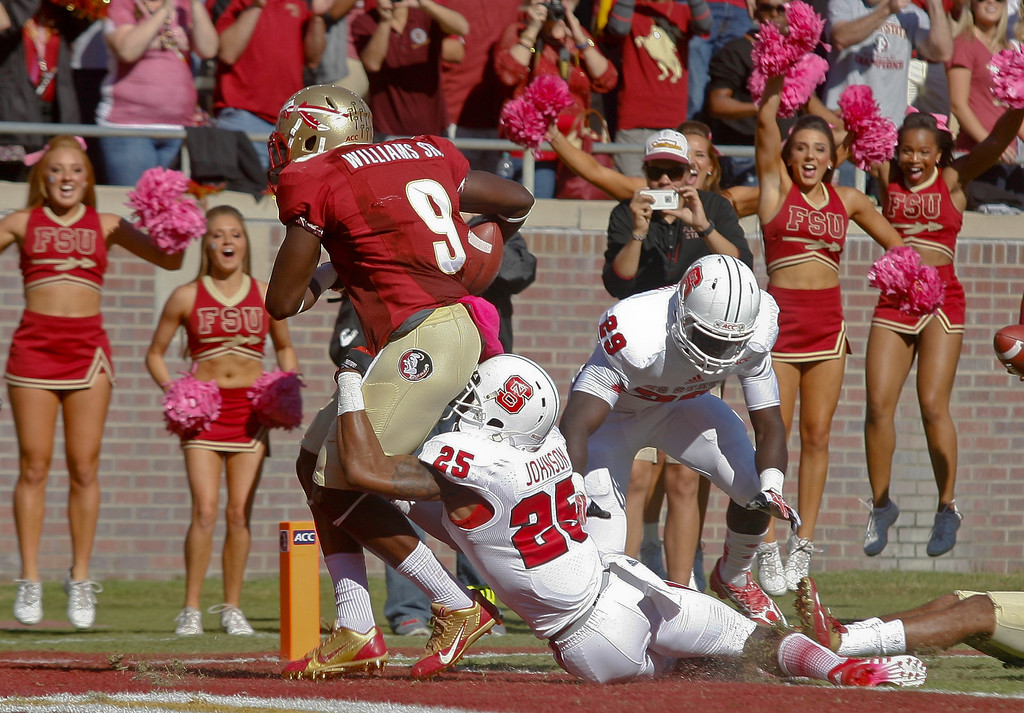 . Florida State running back Karlos Williams (9) drags North Carolina State cornerback Dontae Johnson (25) into the end zone on an 18-yard touchdown in the first quarter of an NCAA college football game on Saturday, Oct. 26, 2013, in Tallahassee, Fla. (AP Photo/Phil Sears)