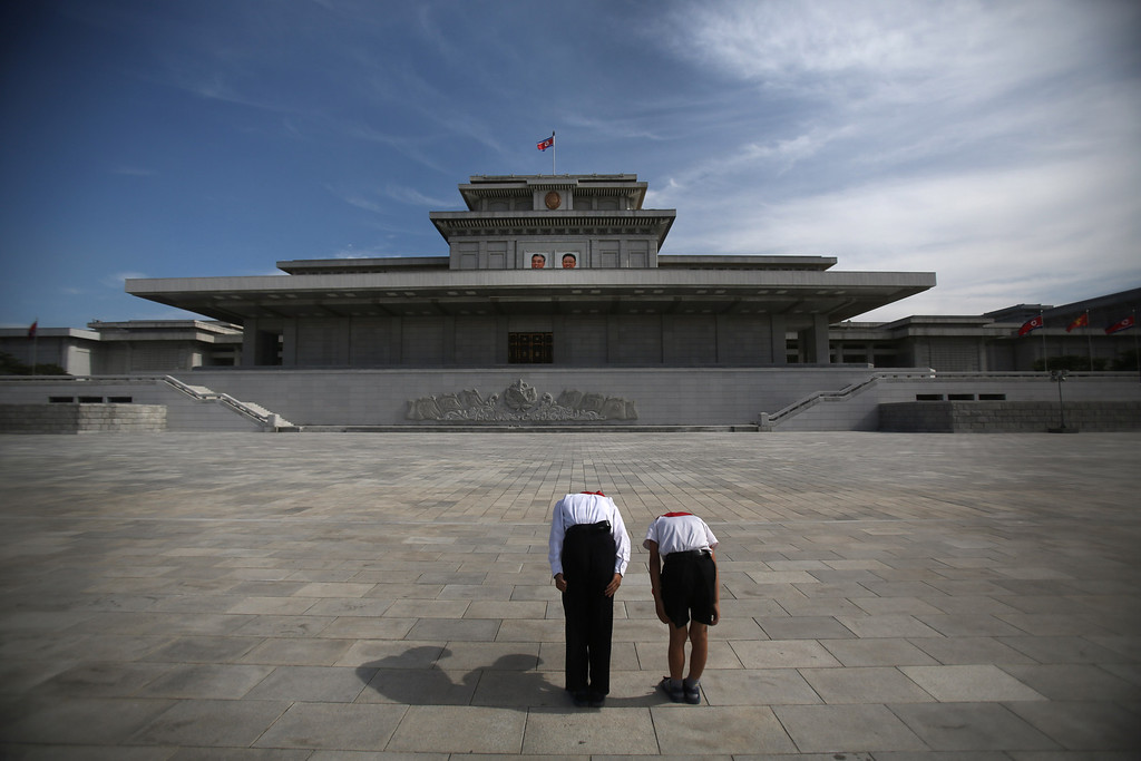 . Two North Korean schoolchildren bow and pay respects to their late leaders Kim Il Sung and Kim Jong Il whose bodies lie embalmed in the mausoleum, the Kumsusan Palace of the Sun, on Thursday, July 25, 2013 in Pyongyang, North Korea. (AP Photo/Wong Maye-E)