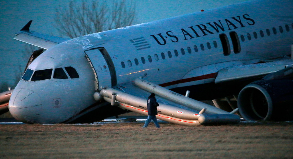 . A person walks around a damaged US Airways jet at the end of a runway at the Philadelphia International Airport, Thursday, March 13, 2014, in Philadelphia. Airline officials said the flight was heading to Fort Lauderdale, Fla., when the pilot was forced to abort takeoff around 6:30 p.m., after the front landing gear failed. An airport spokeswoman said no injuries have been reported. (AP Photo/Matt Slocum)