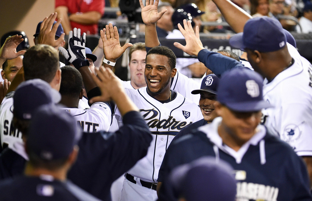 . SAN DIEGO, CA - AUGUST 12:  Rymer Liriano #7 of the San Diego Padres, center, is congratulated in the dugout after scoring on a sacrifice fly ball during the fourth inning of a baseball game against the Colorado Rockies at Petco Park August, 12, 2014 in San Diego, California.  (Photo by Denis Poroy/Getty Images)