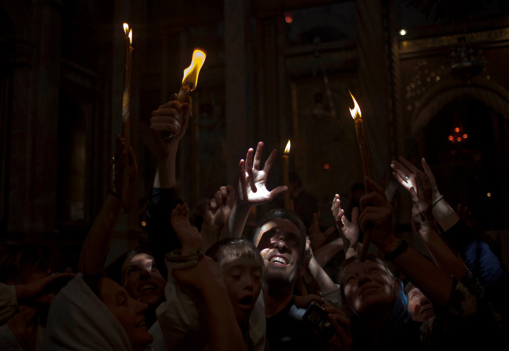 . Christian Orthodox pilgrims raise their hands  towards a beam of light at the Church of the Holy Sepulcher, traditionally believed to be the site of the crucifixion of Jesus Christ, during the ceremony of the Holy Fire in Jerusalem\'s Old City Saturday, May 4, 2013. The Holy Fire ceremony is part of Orthodox Easter rituals and the flame symbolizes the resurrection of Christ. The ceremony dates back to the 12th century. (AP Photo/Ariel Schalit)