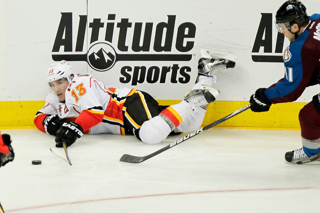 . Calgary Flames\' Mike Cammalleri (13) slides across the ice with Colorado Avalanches\' Jamie McGinn in tow during the third period of an NHL hockey game on Friday, Nov. 8, 2013, in Denver. The Avalanche won 4-2. (AP Photo/Barry Gutierrez)