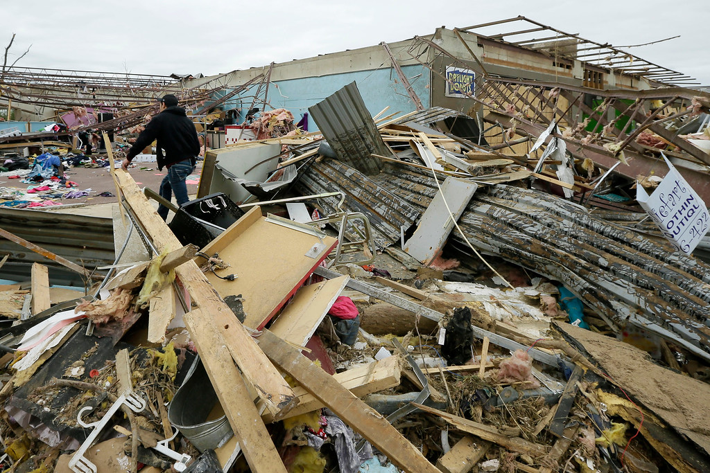 . A man walks through rubble of the Vilonia Shopping Center in Vilonia, Ark., Wednesday, April 30, 2014. A tornado struck the town late Sunday.  Along stretches of damaged houses, volunteers with chain saws cleared trees from across homes, driveways and streets.  (AP Photo/Danny Johnston)
