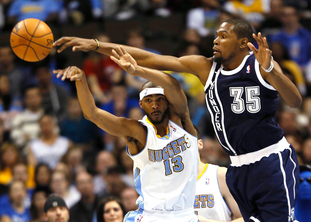 . Denver Nuggets\' Corey Brewer (L) is defended by Oklahoma City Thunder\'s Kevin Durant in their NBA basketball game in Denver March 1, 2013. REUTERS/Rick Wilking