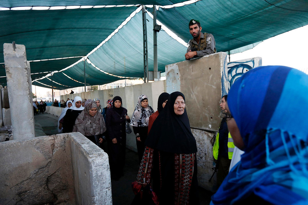 . An Israeli border policeman (top) stands guard as Palestinians cross an Israeli checkpoint in the West Bank town of Bethlehem, during the holy month of Ramadan July 26, 2013. REUTERS/Baz Ratner