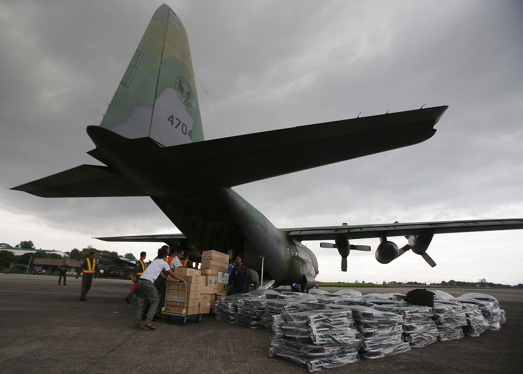 . Members of the Philippine Air Force and volunteers load medical supplies, relief goods and cots on to a C-130 military plane as they prepare to fly to quake-hit Bohol island at Villamor Air Base in  Pasay, south of Manila on Thursday, Oct. 17, 2013.  (AP Photo/Aaron Favila)