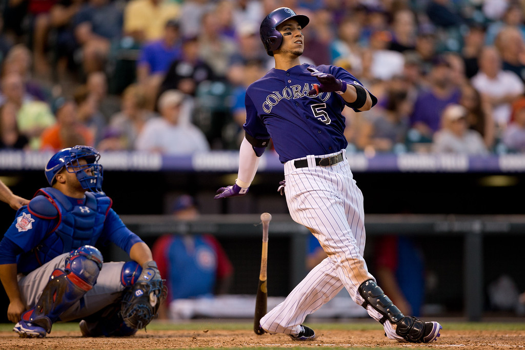 . DENVER, CO - JULY 20:  Carlos Gonzalez #5 of the Colorado Rockies hits a solo home run during the fifth inning as catcher Welington Castillo #53 of the Chicago Cubs looks on at Coors Field on July 20, 2013 in Denver, Colorado.  (Photo by Justin Edmonds/Getty Images)
