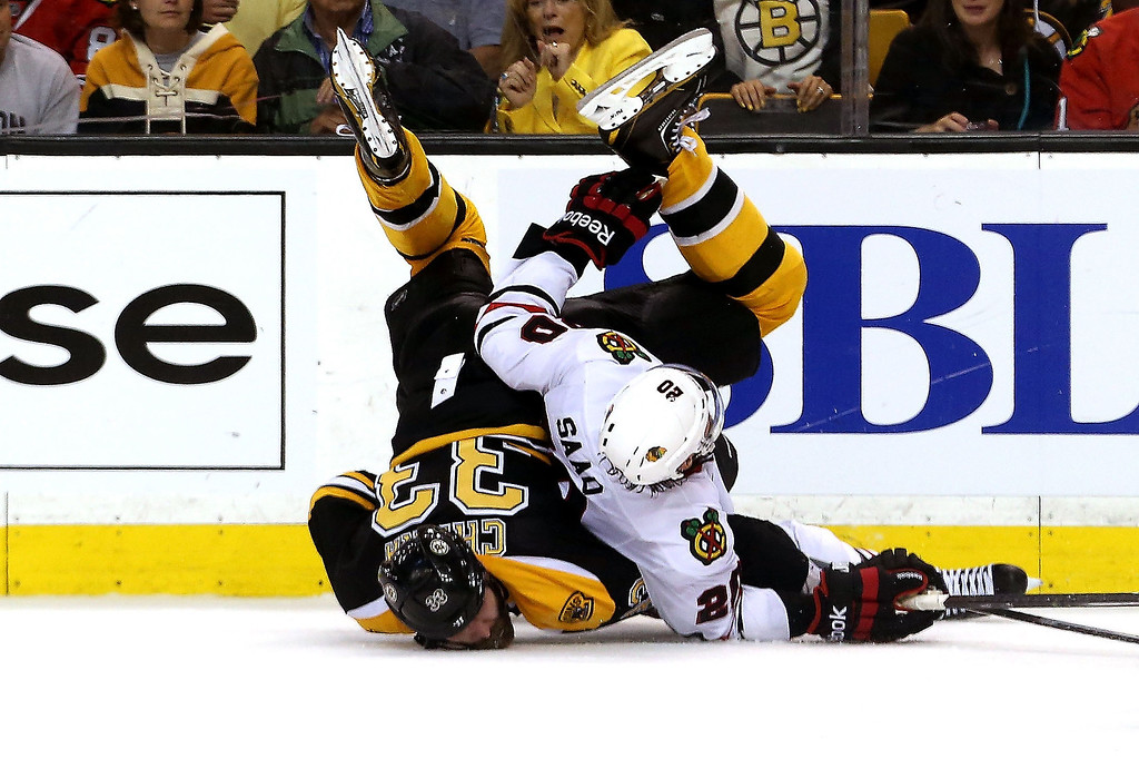 . Zdeno Chara #33 of the Boston Bruins and Brandon Saad #20 of the Chicago Blackhawks fall to the after a check in Game Six of the 2013 NHL Stanley Cup Final at TD Garden on June 24, 2013 in Boston, Massachusetts.  (Photo by Bruce Bennett/Getty Images)
