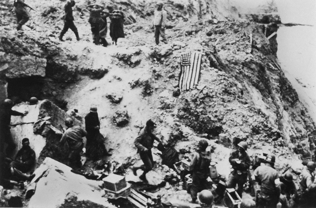 . U.S. soldiers from the 2nd Ranger Battalion surround German prisoners June 6, 1944 on the Pointe du Hoc located on a cliff which overlooks Omaha Beach after Allied forces stormed the Normandy beaches during D-Day. Elements of the 2nd Ranger Battalion scaled the 100 foot cliff and seized the German artillery pieces that could have fired on the Allied forces landing at Omaha Beach.   ( -/AFP/Getty Images)