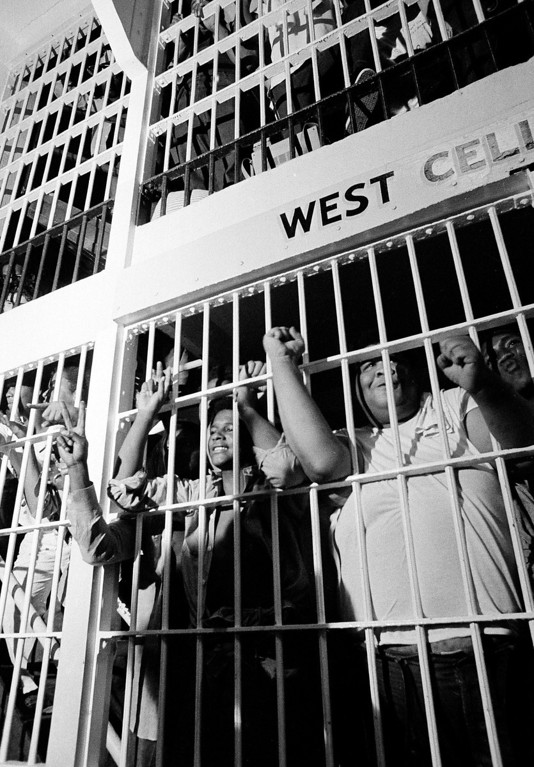""". In this July 28, 1973 file photo, convicts give the \""""V\"""" for victory and clenched fist sign to newsmen who were allowed to view the West Cell Block at Oklahoma State Prison, as rioting subsided and many returned to their cells. The OSP had 2,200 inmates at the time, twice its capacity. The prison erupted into violence on July 27, 1973, the result of overcrowding, inadequate supervision, poor health care and a culture of violence within the prison walls. (AP Photo/Staff, File)"""