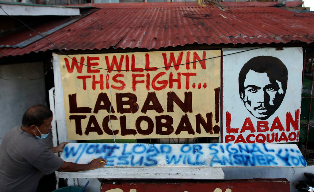 . A Filipino typhoon victim, Cesar Cayanong, 59, is seen in front of a signage portraying Filipino icon boxer Manny Pacquiao, at a street in the super typhoon devastated town of Mayorga, Samar island province, the Philippines, 21 November 2013. The Philippine government on 21 November 2013, turned its attention to the reconstruction of cities and town devastated by Typhoon Haiyan, which killed over 4,000 people and displaced more than four million.  EPA/RITCHIE B. TONGO
