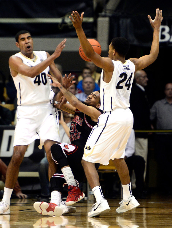 . University of Colorado\'s Josh Scott (40) and George King (24) strip the ball from Arkansas State\'s Melvin Johnson (31) during their game at the Coors Event Center on the CU Boulder Campus in Boulder, Colorado on November 18, 2013.  Photo by Paul Aiken / The Boulder Daily Camera.