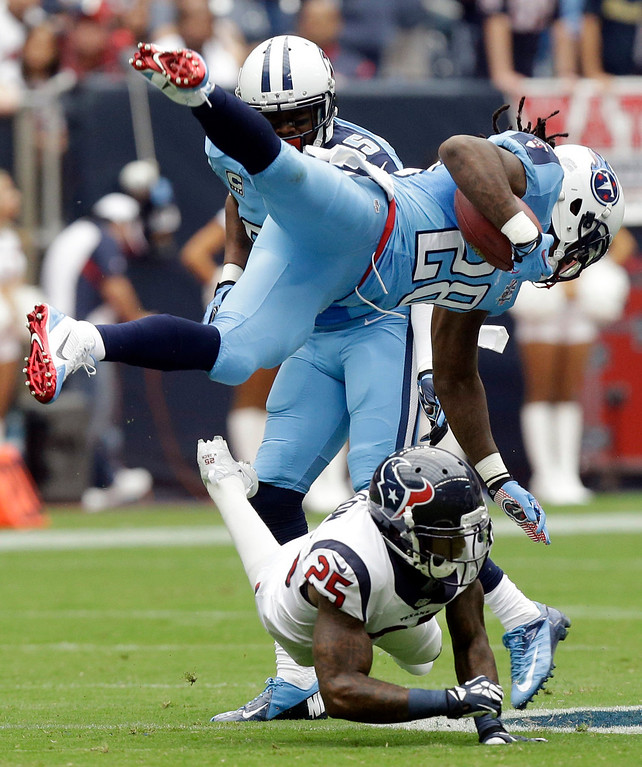 . Tennessee Titans\' Chris Johnson (28) is upended by Houston Texans\' Kareem Jackson (25) during the first quarter of an NFL football game Sunday, Sept. 15, 2013, in Houston. (AP Photo/Patric Schneider)
